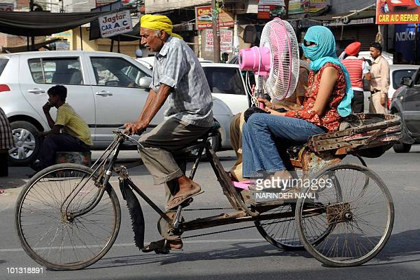 An Indian women holds a fan while travelling on a rickshaw in Amritsar on June 1 2010 An extreme heat wave scorching northern India is taking its...