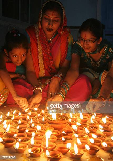 An Indian women lights clay lamps 'diya' in Siliguri 09 November 2007 as they take part in celebrations for the Hindu Festival of Diwali the Festival...