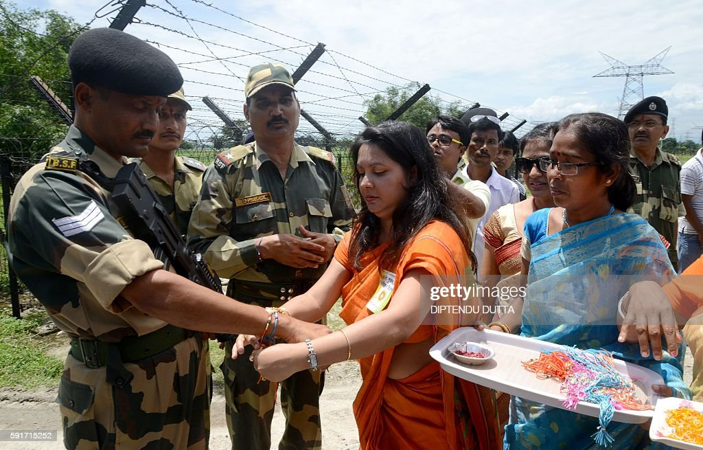 An Indian women ties a 'rakhi' or sacred thread onto the wrist of an Indian Border Security Force personnel on the occasion of the Hindu festival...