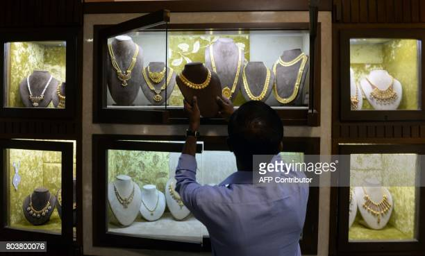 An Indian worker adjusts jewels at a jewellery store in Chennai on June 30 2017 India is bracing for its most significant reform in a generation as...