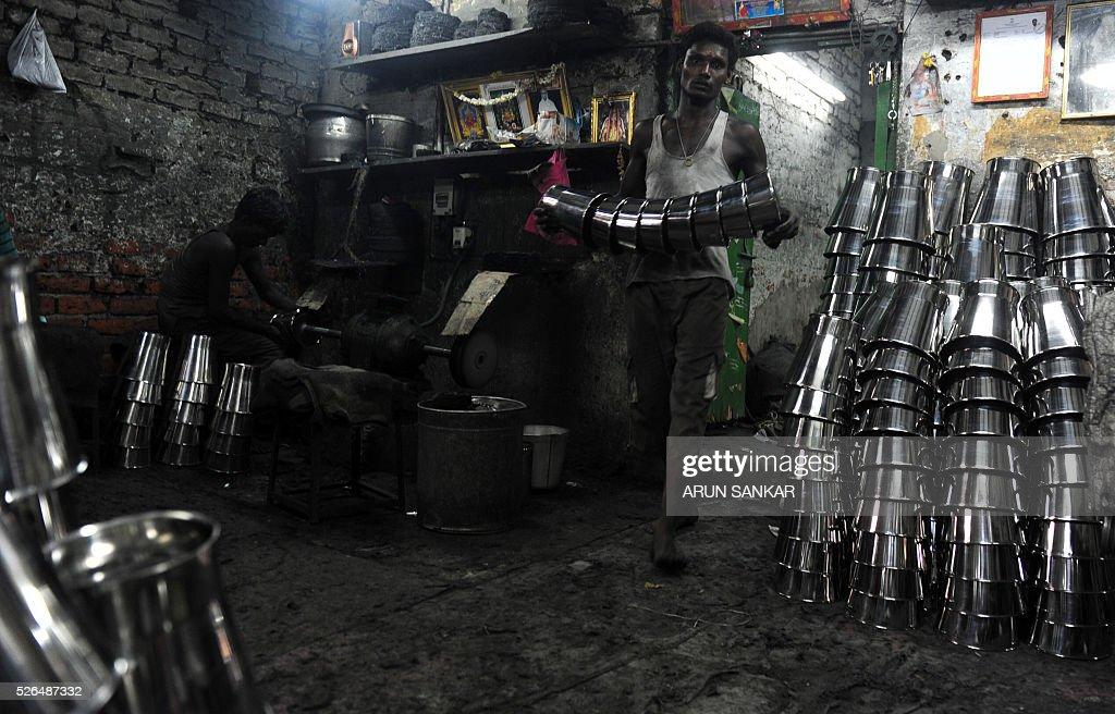 An Indian worker carries a set of finished stainless steel utensils at a metal workshop in Chennai on April 30, 2016,on the eve of International Labour Day. / AFP / ARUN