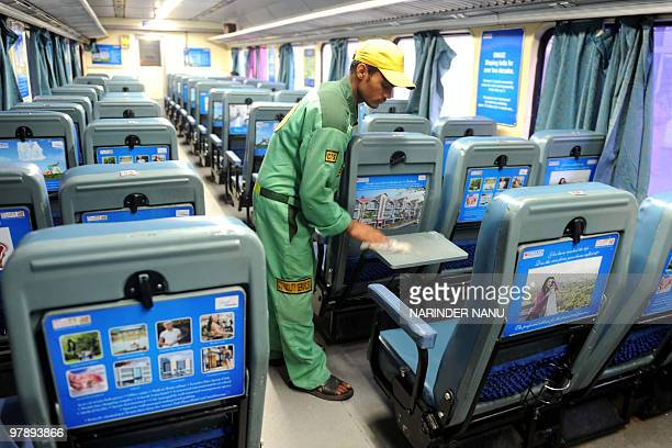 An Indian worker cleans a carriage of a newlylaunched train stationed at a train station in Amritsar on March 20 2010 The company Omaxe launched the...