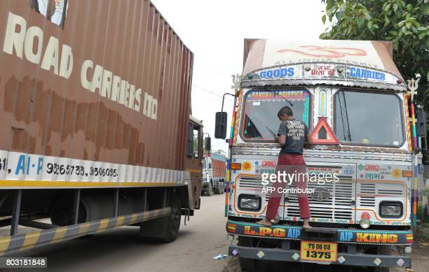 An Indian worker cleans a lorry parked on the outskirts of Hyderabad on June 29 2017 India is bracing for its most significant reform in a generation...