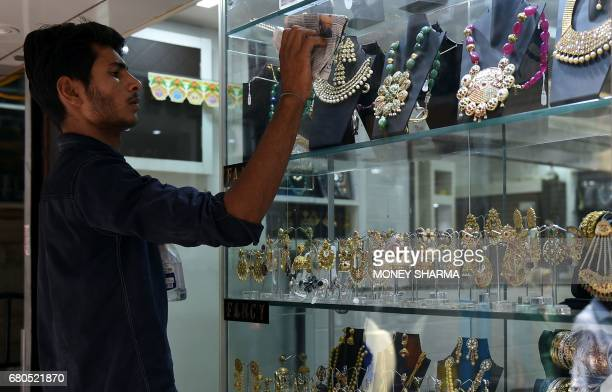 An Indian worker cleans the window pane of a jewellery shop in New Delhi on May 8 2017 Fat wads of bank notes move across counters in Old Delhi's...