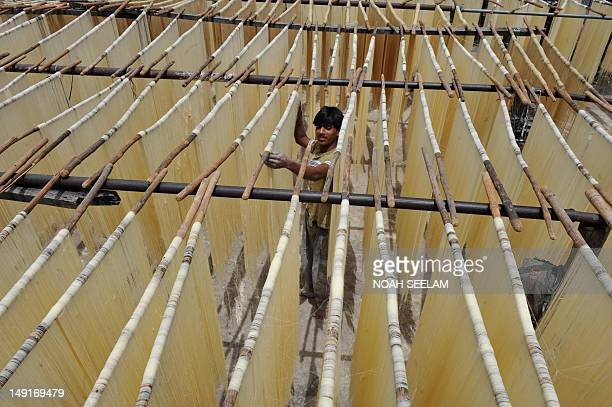 An Indian worker dries Seviiyan thin vermicelli which is used for the preparation of sheerkhorma a traditional sweet dish prepared by the Muslim...