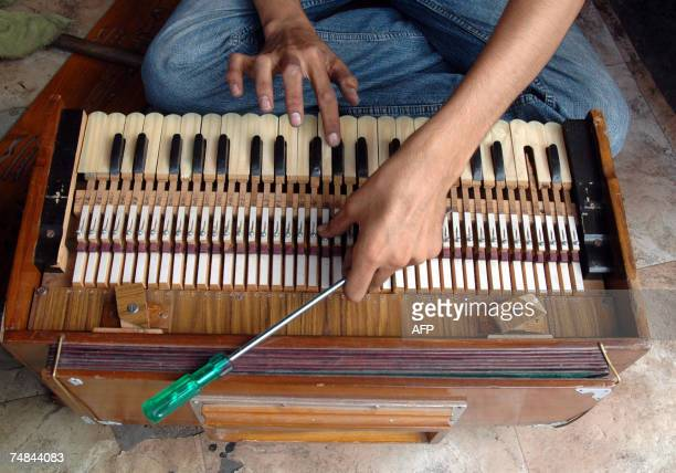 An Indian worker fixes the reeds of a harmonium at his shop in Hyderabad 21 June 2007 on the occasion of the world's music day celebrated worldwide...