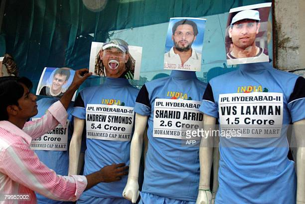 An Indian worker from a garment shop adjusts a display of mannequins bearing images of Indian Premier League Hyderabad team cricketers in a street of...