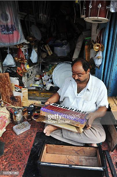 An Indian worker inspects a harmonium at a musical instrument workshop in Hyderabad on June 21 2010 World Music Day is celebrated annually on June 21...