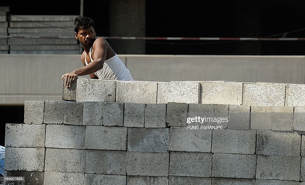 An Indian worker off-loads stone blocks at a construction site near the international airport in Mumbai on March 19, 2013. India's central bank cut its main interest rate by 25 basis points on March 19, its second such reduction this year in an effort to jumpstart the slowing economy. AFP PHOTO/PUNIT PARANJPE