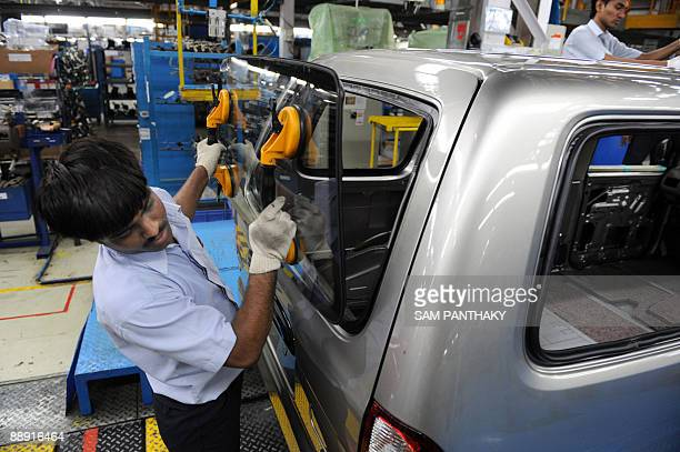 An Indian worker places a rear windscreen onto a car at The General Assembly Section at the General Motors India plant at Halol some 160 kms from...