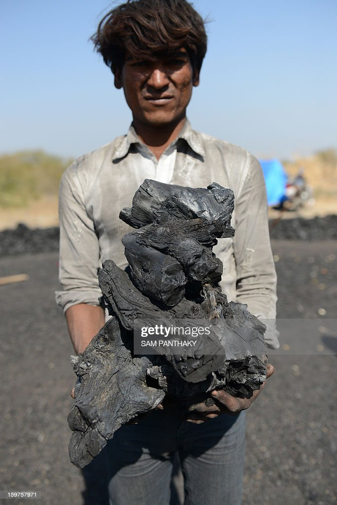 an Indian worker poses with charcoal made by burning local bawal wood near Khanderaopura village of Kadi Taluka, some 40 kms. from Ahmedabad, on January 19, 2013. Wood charcoal as a source of fuel and warmth is in high demand across many parts of India during the winter season. AFP PHOTO / Sam PANTHAKY