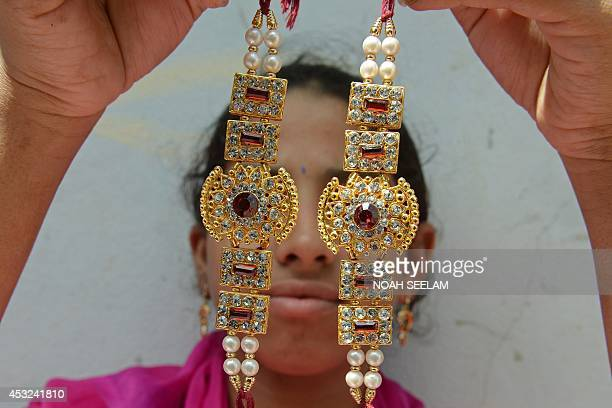 An Indian worker poses with specially designed bracelets called rakhis at the Amrut rakhi workshop in Hyderabad on August 6 ahead of the Raksha...