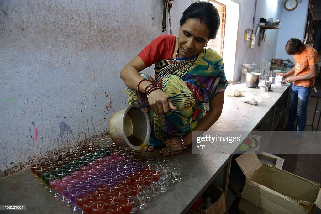 An Indian worker pours coloured hot wax into glasses to make decorative wax candles of the forthcoming Christmas festivities at The R A Matcheswala Cottage Industry in Ahmedabad on December 18, 2012. Christians celebrate the birth of Jesus Christ on December 25. AFP PHOTO/Sam PANTHAKY