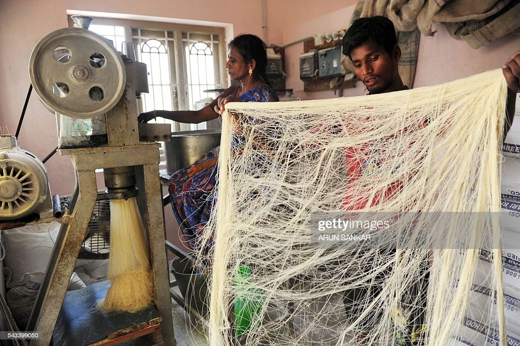 An Indian worker prepares strands of drying seviiyan - thin vermicelli - which is used for the preparation of 'sheerkhorma', a traditional sweet dish prepared by muslims during the holy month of Ramadan, at a food factory in Chennai on June 28, 2016. Muslims around the world celebrate the month of Ramadan by abstaining from eating, drinking, and smoking as well as sexual activities from dawn to dusk. / AFP / ARUN