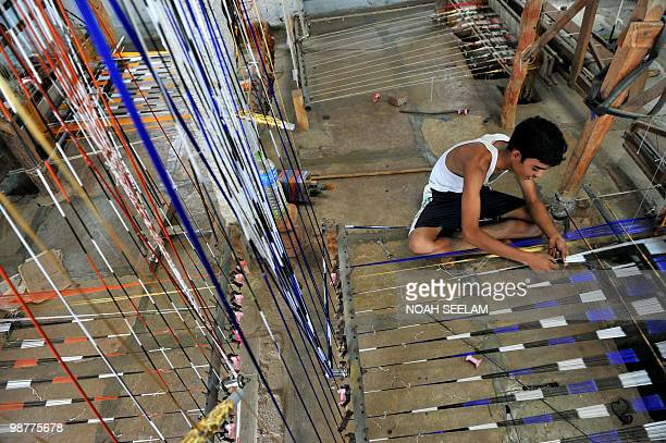 An Indian worker prepares threads before weaving on a hand loom in a workshop at Bhoodan Pochampally in Nalgonda District some 55 kms from Hyderabad...