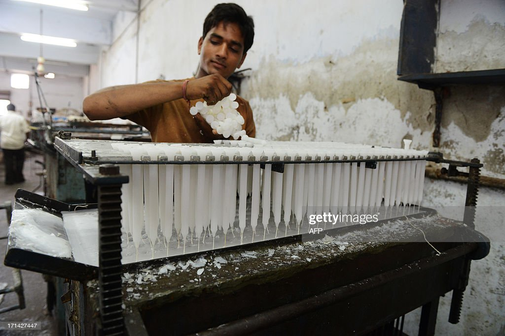An Indian worker prepares wax candles at a factory in Ahmedabad on June 24, 2013. Wax candles are in great demand during the monsoon season when electricity blackouts are more common because of heavy rain. AFP PHOTO / Sam PANTHAKY