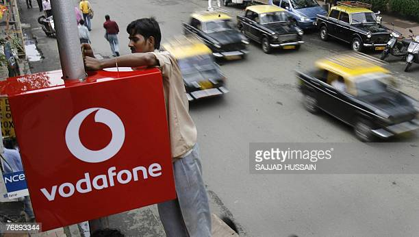 An Indian worker puts up the logo of telecom firm 'Vodafone' outside the corporate office in India's financial capital Mumbai 20 September 2007...