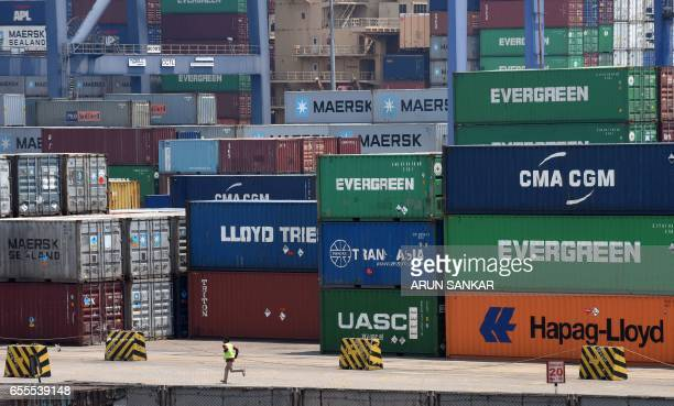 An Indian worker runs through a container terminal in Chennai on March 20 2017 Indian Directorate of Revenue Intelligence and customs officials are...