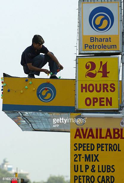 An Indian worker sets decorative lights atop a petrol station in New Delhi 01 November 2004 Soaring global crude prices could hit growth and lead to...