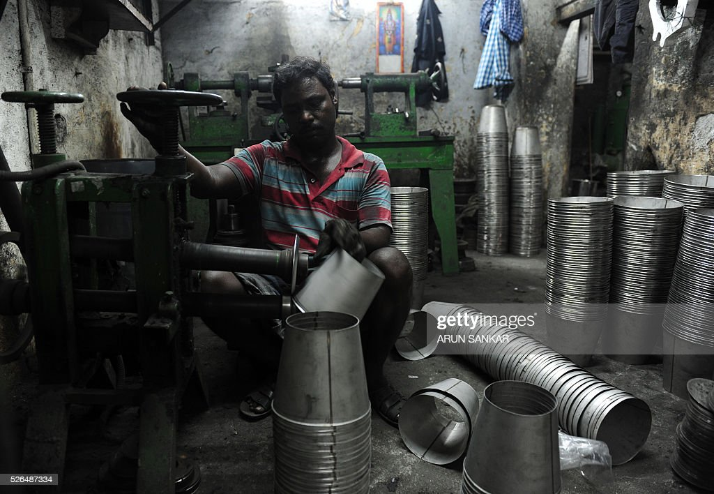 An Indian worker shapes aluminium utensils at a metal workshop in Chennai on April 30, 2016, on the eve of International Labour Day. / AFP / ARUN