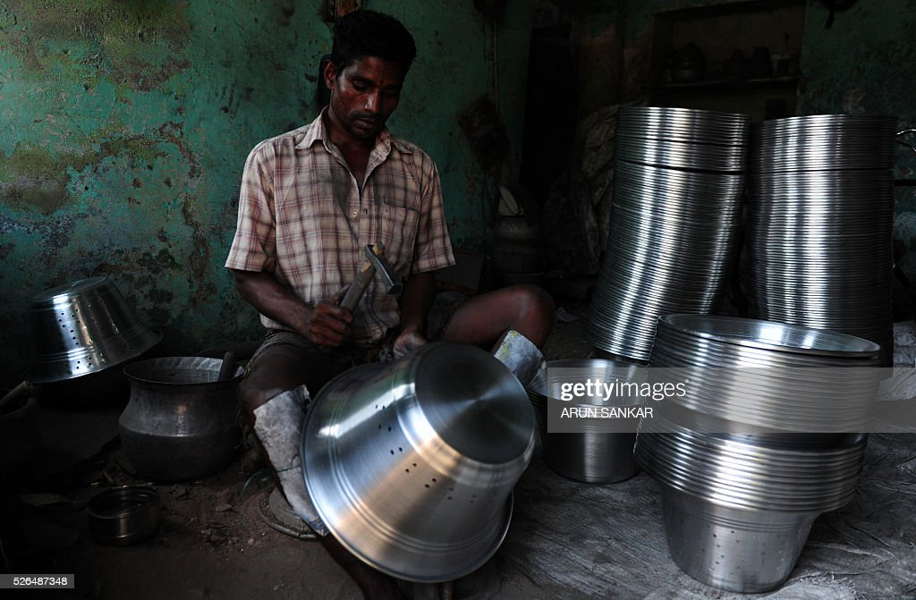 An Indian worker shapes aluminium utensils at a metal workshop in Chennai on April 30, 2016,on the eve of International Labour Day. / AFP / ARUN