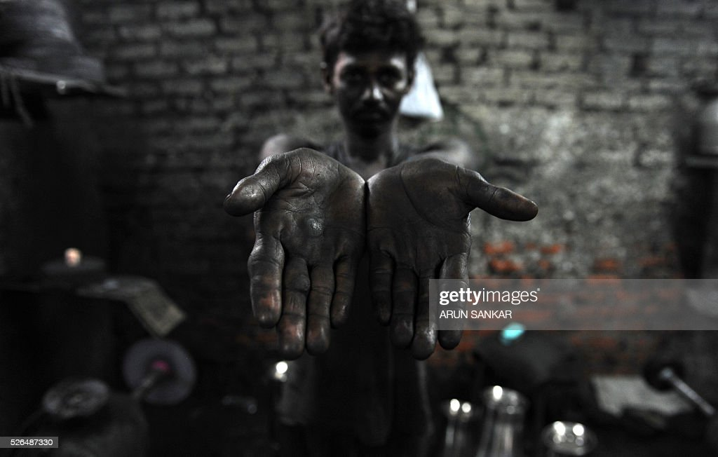 An Indian worker shows his grease stained hands at a metal utensil workshop in Chennai on April 30, 2016,on the eve of International Labour Day. / AFP / ARUN