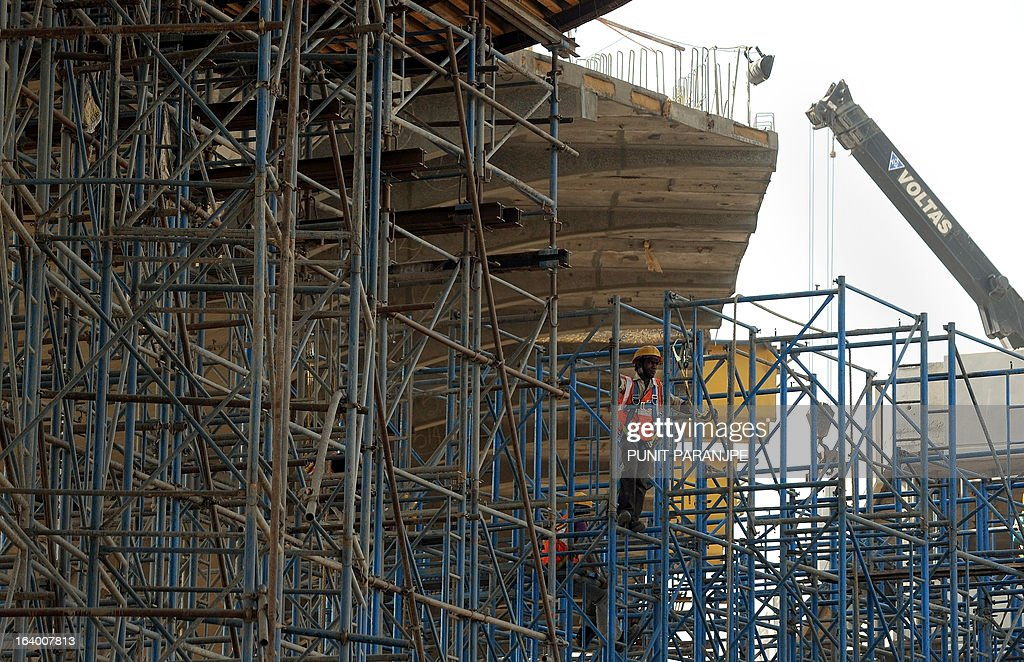 An Indian worker stands on scaffolding at a construction site near the international airport in Mumbai on March 19, 2013. India's central bank cut its main interest rate by 25 basis points on March 19, its second such reduction this year in an effort to jumpstart the slowing economy. AFP PHOTO/PUNIT PARANJPE