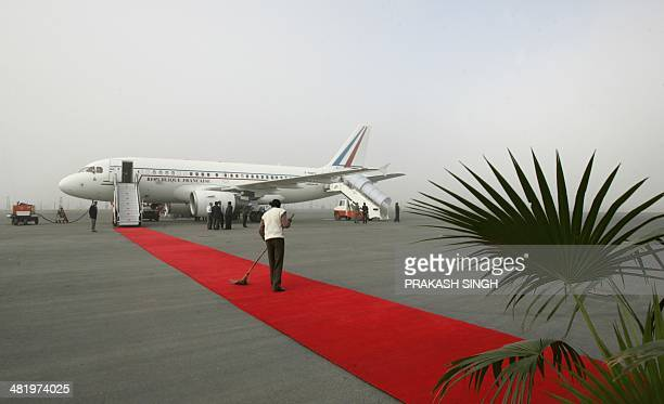 An Indian worker sweeps the red carpet leading to a French aircraft sitting on the tarmac prior to the departure of French President Jacques Chirac...