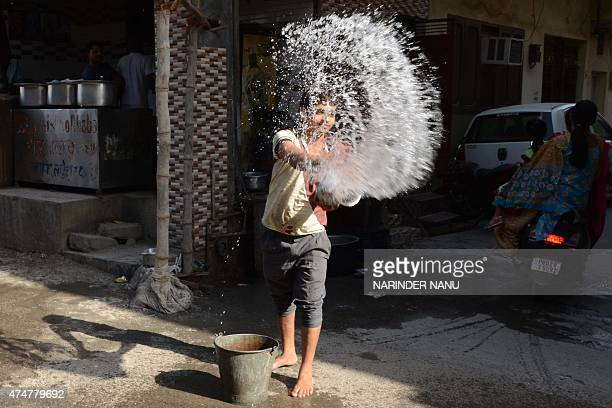 An Indian worker throws water outside a resteraunt in Amritsar on May 26 in an attempt to keep the pavement cool on a hot day At least 800 people...
