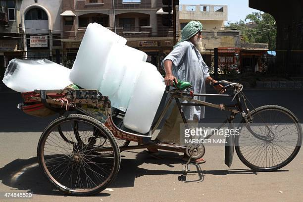An Indian worker uses a ricksahw to transport ice from an ice factory in Amritsar on May 27 2015 More than 1100 people have died in a blistering...