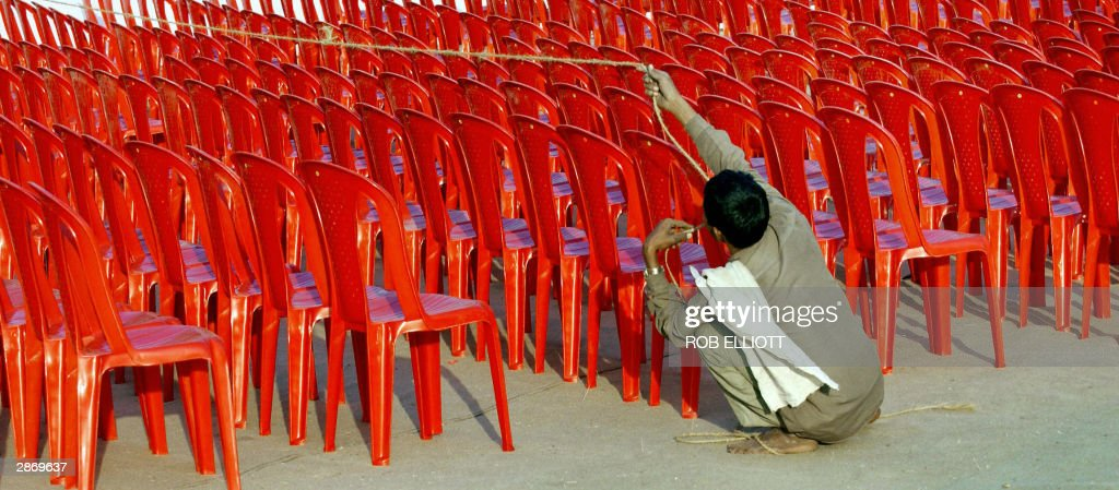 An Indian worker uses a rope to lineup red plastic chairs in the seating area of the main stage at the World Social Forum site in Bombay 15 January...