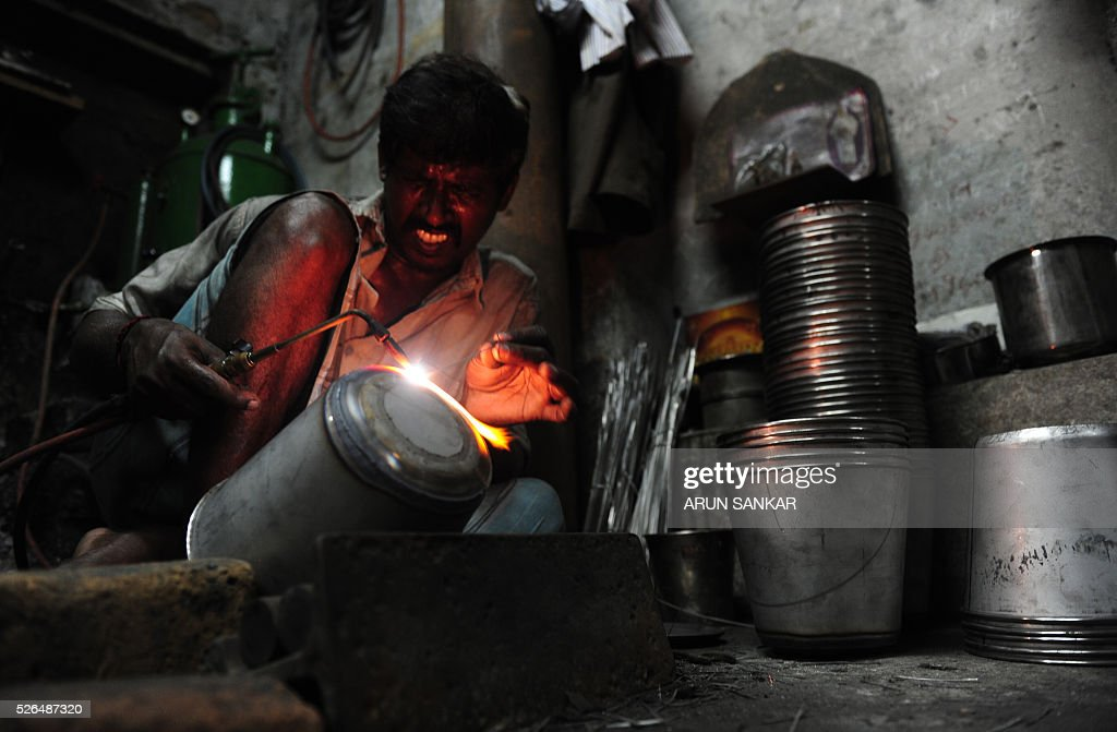 An Indian worker welds stainless steel utensils at a metal workshop in Chennai on April 30, 2016, on the eve of International Labour Day. / AFP / ARUN