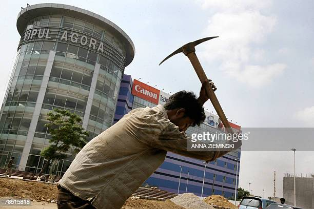 An Indian worker wields a pickaxe outside an upmarket shopping mall under construction in the satellite town of Gurgaon on the outskirts of New Delhi...