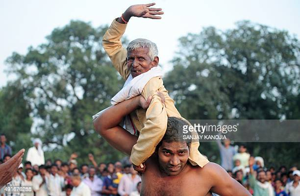 An Indian wrestler lifts an elderly villager after victory during a traditional wrestling competition at a fair held annually on October 7 in Rampur...