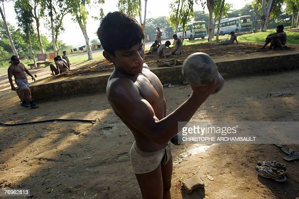 An Indian wrestler lifts weights as he warms up ahead of a practice session at an Akhara ground on the outskirts of New Delhi 22 September 2007...