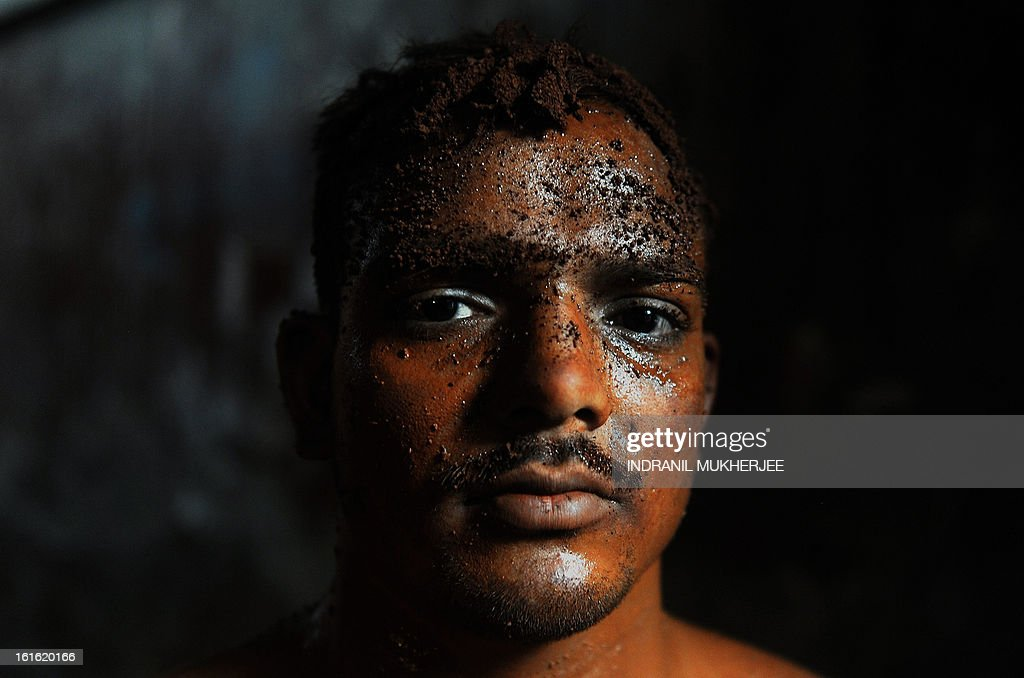 An Indian wrestler looks on after an evening practice session at the Mahatma Phule Vyayam Mandir Kushti (traditional Indian wrestling) academy in Mumbai on February 13, 2013. Wrestlers around the world on Wednesday vowed to fight to save the ancient sport's Olympic status, after the International Olympic Committee voted to drop it for the 2020 Games. AFP PHOTO/Indranil MUKHERJEE