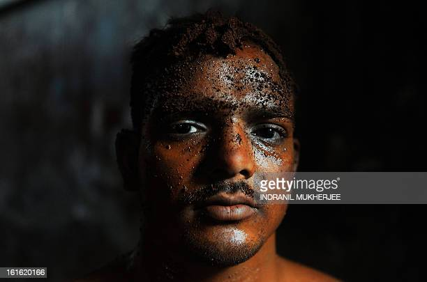 An Indian wrestler looks on after an evening practice session at the Mahatma Phule Vyayam Mandir Kushti academy in Mumbai on February 13 2013...