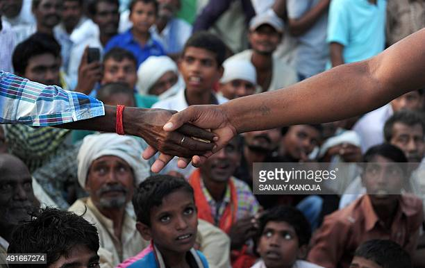 An Indian wrestler receives prize money from the crowd after victory during a traditional wrestling competition at a fair held annually on October 7...