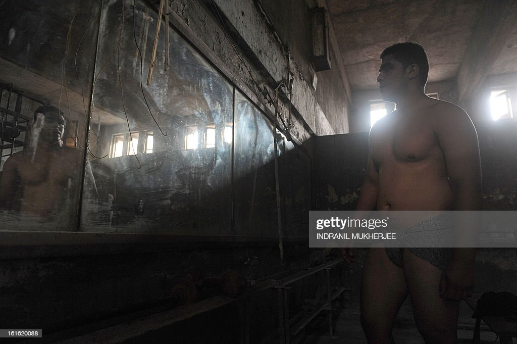 An Indian wrestler warms up in front of a mirror before an evening practice session at the Mahatma Phule Vyayam Mandir Kushti (traditional Indian wrestling) academy in Mumbai on February 13, 2013. Wrestlers around the world on Wednesday vowed to fight to save the ancient sport's Olympic status, after the International Olympic Committee voted to drop it for the 2020 Games. AFP PHOTO/Indranil MUKHERJEE