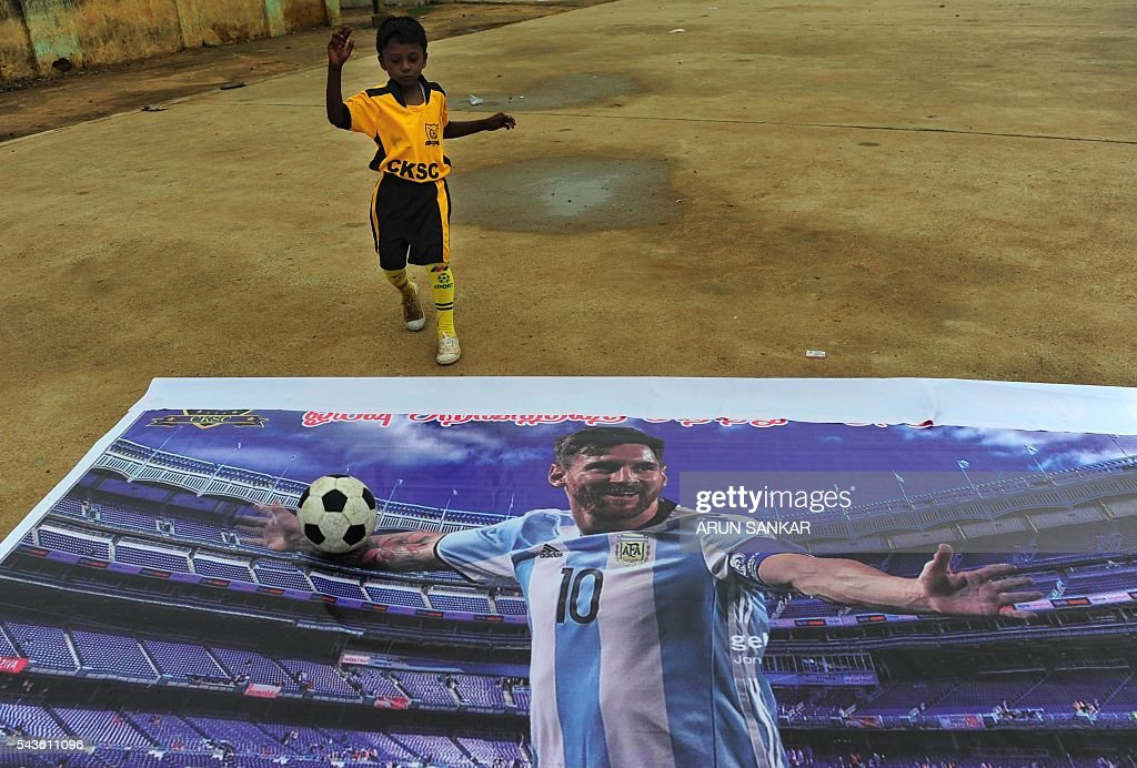 An Indian youth chases a football over a poster of Argentinian footballer, Lionel Messi displayed at a football ground and saying that Messi should come back, in Chennai on June 29, 2016. Argentina was defeated in the Copa America final against Chile, 4-2, in a penalty shoot-out. Argentinians begged Lionel Messi - who tearfully decided to quit the international team after missing a spot-kick in the shootout - not to leave the national team despite its traumatic final. / AFP / ARUN
