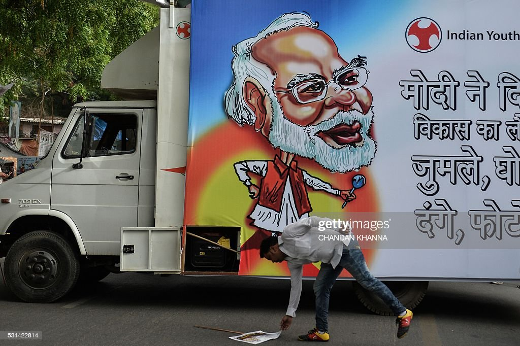 An Indian Youth Congress (IYC) activist picks up a placard during a protest following the completion of two years of the Narendra Modi-led National Democratic Alliance (NDA) in New Delhi on May 26, 2016. Prime Minister Narendra Modi has defended his record of reforming India's stuttering economy after two years in power, but conceded that his right-wing government faced 'an enormous task ahead'. KHANNA