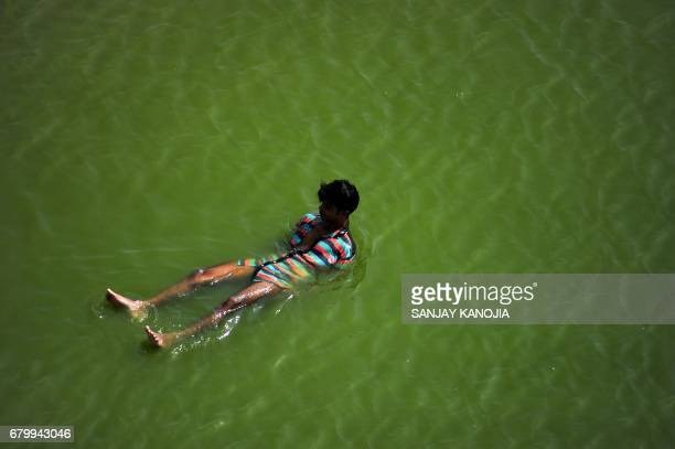 An Indian youth cools off in the Yamuna river in Allahabad on May 72017 / AFP PHOTO / Sanjay KANOJIA