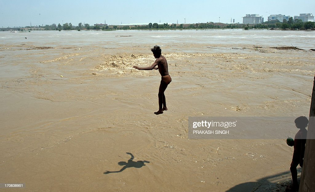 An Indian youth dives into the rising waters of the Yamuna river in New Delhi on June 19, 2013. The monsoon, which India's farming sector depends on, covers the subcontinent from June to September, usually bringing some flooding. But the heavy rains arrived early this year, catching many by surprise and exposing the country's lack of preparedness. Military helicopters dropped emergency supplies to thousands of tourists and pilgrims stranded by flash floods that tore through towns and temples in northern India, killing at least 120 people, officials said. AFP PHOTO/ Prakash SINGH