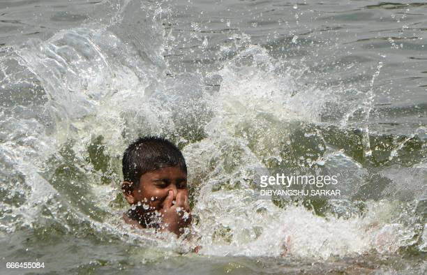 An Indian youth jumps into a lake amid rising temperatures in Kolkata on April 9 2017 Temperatures rose to nearly 40 degrees in Kolkata and are set...