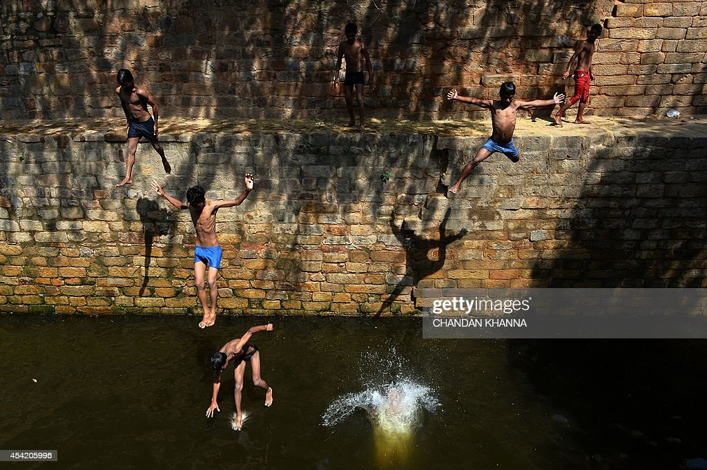An Indian youth jumps into the water at the Gandak ki Baoli, 'a well with steps' which was constructed during the rule of Emperor Iltutmish who was also the founder of the slave dynasty, in New Delhi on August 26, 2014. Emperor Iltutmish founded the Delhi Sultanate and ruled from 1211. AFP PHOTO/ Chandan KHANNA