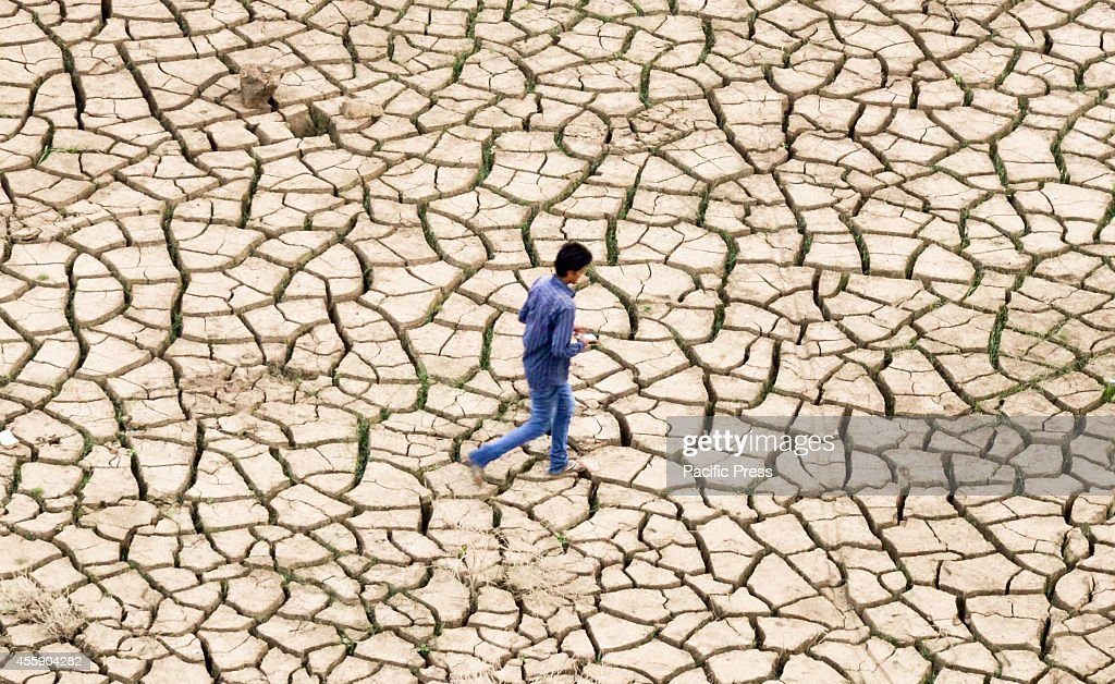 An Indian youth walks over dried mud on the banks of a river after waters from the seasonal monsoon rains receded in Allahabad The southwest monsoon...
