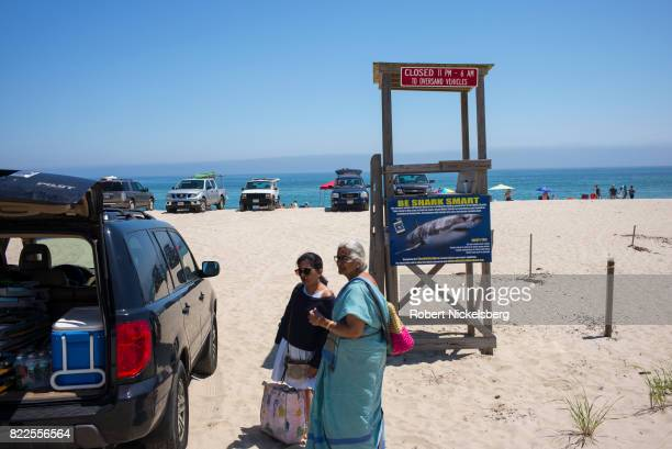 An IndianAmerican family unloads their car while at the beach in East Orleans Massachusetts July 16 2017 A sign warning of sharks offshore is...
