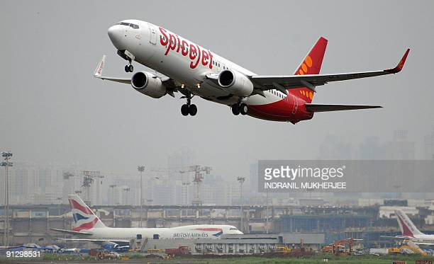 An Indianoperated SpiceJet Boeing 737800 aircraft takes off as a British Airways Boeing 747400 aircraft sits on the tarmac at the international...
