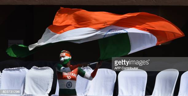 An India's cricket fan waves his country's national flag during the third day of the first Test match between Sri Lanka and India at Galle...