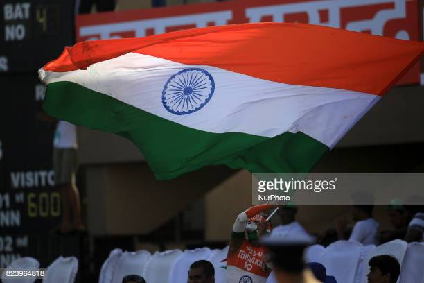 An India's cricket fan waves the Indian national flag before the beginning of the 3rd Day's play in the 1st Test match between Sri Lanka and India at...